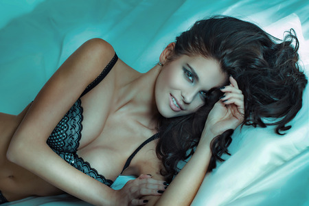 erotic woman: Sensual beautiful brunette woman posing in lingerie, lying in bed, smiling to the camera. Stock Photo