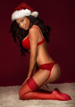 naked young women: Чувственный сексуальная женщина позирует голый с шляпу Санта-Клауса. Брюнетка девушка в красном нижнем белье.