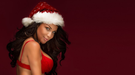 nude christmas: Portrait of brunette sexy woman with red Santa Claus hat. Christmas content.