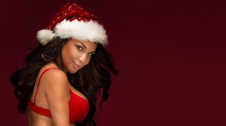 modelos desnudas: Retrato de la mujer atractiva morena con sombrero rojo de Santa Claus. contenido de la Navidad.