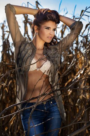 Sexy brunette woman posing in lingerie over corn field. Autumn.