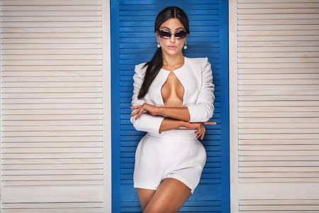 naked sexy women: Sexy fashionable woman posing in sunglasses, wearing white costume. Girl with black long hair. Studio shot.