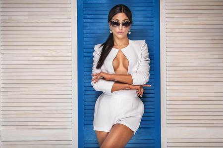 sexy nackte frau: Sexy modische Frau posiert mit Sonnenbrille, tragen weiße Kostüm. Mädchen mit dem schwarzen langen Haar. Studio gedreht. Lizenzfreie Bilder