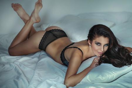 modelo desnuda: Sensual mujer hermosa morena posando en ropa interior, en la cama, sonriendo a la cámara.