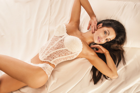 brunette naked: Sensual beautiful brunette woman posing in lingerie, lying in bed, smiling to the camera. Stock Photo