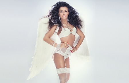 nude sexy woman: Romantic sensual brunette lady posing in white lingerie and big wings. Angel in heaven.
