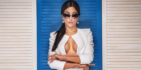 sexy nude women: Sexy fashionable woman posing in sunglasses, wearing white costume. Girl with black long hair. Studio shot.