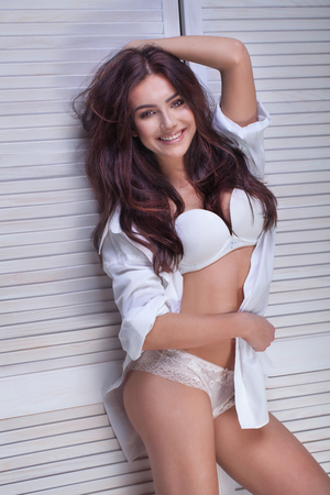 glamour nude: Sensual romantic woman posing in white lingerie, smiling to the camera.