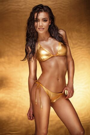 junge nackte m�dchen: Beautiful young brunette girl posing in gold swimsuit. Studio shot.