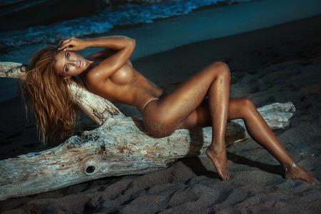 Сексуальная блондинка позирует голой женщины на пляже. Идеальный тонкий корпус. Фото со стока