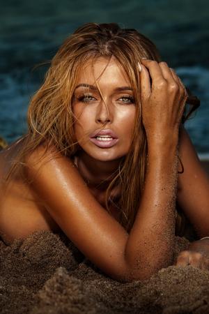 fille nue sexy: Portrait de femme blonde sexy allongé sur la plage.