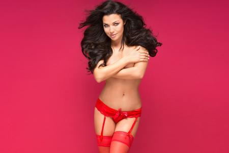 modelos desnudas: Mujer morena sexy posando en ropa interior roja y medias, mirando a la cámara. Corporal ideal Slim. Fondo rojo.