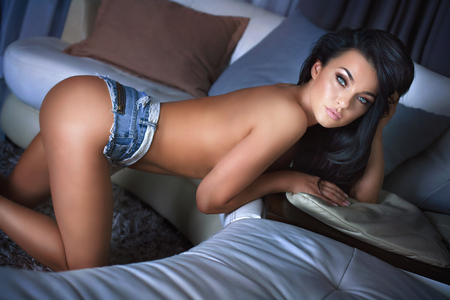 naked: Sexy naked woman with black hair and glamour makeup posing in room, wearing just short jeans, showing her ideal slim body.
