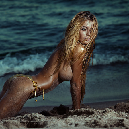 Beautiful sexy blonde woman posing topless on the beach. Girl with long wet hair looking at camera.