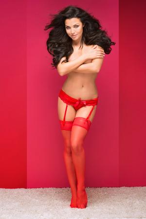 modelos desnudas: Mujer morena sexy posando en ropa interior roja y medias, mirando a la cámara. Corporal ideal Slim. Foto completa. Fondo rojo.