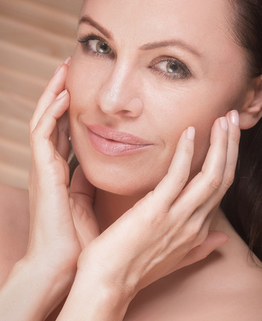 natural looking: Closeup beauty portrait of attractive natural brunette woman. Woman looking at camera, holding hands on face. Cute smile.
