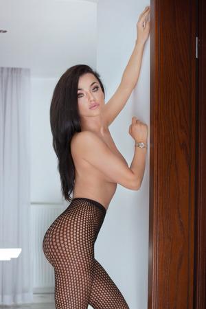 mujeres desnudas: Sexy mujer de fascinación posando en ropa interior erótica, mirando a la cámara. Chica con el pelo largo negro y maquillaje glamour.