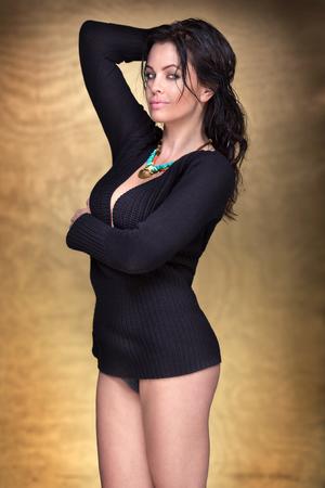 femme brune sexy: Femme sexy posant en studio sur fond d'or, en regardant la caméra. Style sensuel.