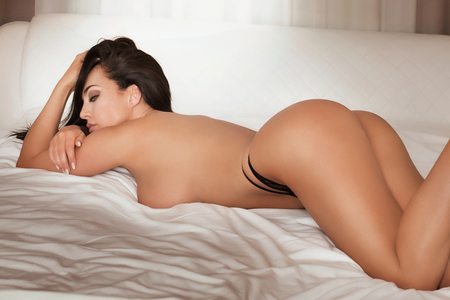 mujeres desnudas: Sexy mujer desnuda en la cama, el uso de tacones altos. Habitación de hotel. Foto de archivo