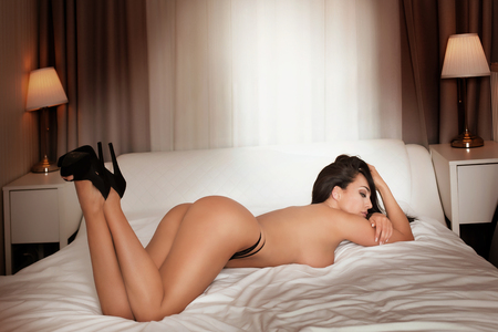 nude breasts: Naked sexy woman lying in bed, wearing high heels. Hotel room. Stock Photo