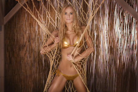beautiful blonde: Beautiful blonde young woman with long hair posing in gold bikini. Summer photo. Sexy woman.