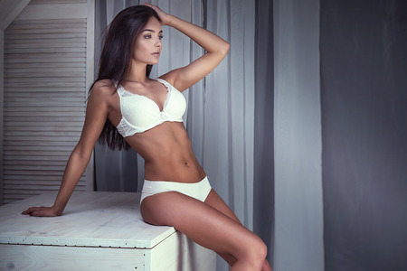undressed: Romantic brunette young woman posing in white lingerie. Indoor photo. Ideal body.