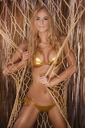 sensual woman: Beautiful blonde young woman with long hair posing in gold bikini. Summer photo. Sexy woman.