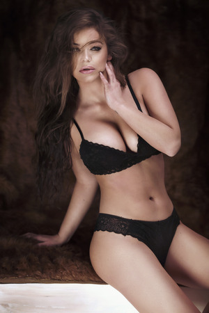 erotic woman: Sexy brunette woman posing in black lingerie, looking at camera. Girl with long hair.