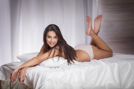 Sensual brunette woman with long slim legs lying in bed, looking at camera.