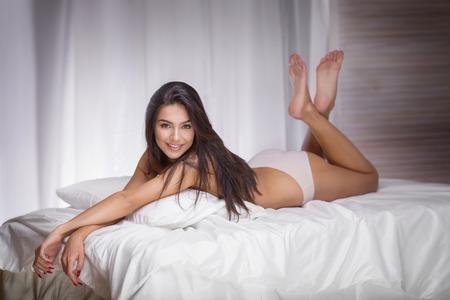 sexy beine: Sinnliche Frau, brünett mit langen schlanken Beinen liegend im Bett, Blick in die Kamera.