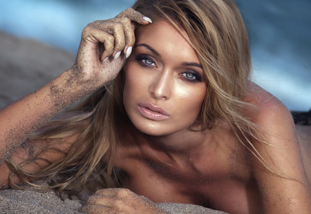 pechos: Retrato de mujer rubia sexy con largas pestañas. Chica posando desnuda, mirando a la cámara. Día de verano.