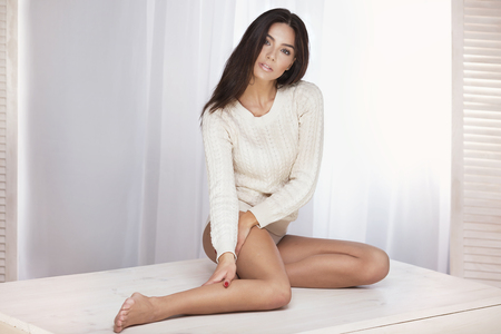 donna ricca: Attractive sexy woman posing in studio. Girl with long hair and perfect fit body. Girl looking at camera, sitting.