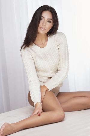 sueteres: Atractiva mujer sexy posando en el estudio. Chica con el pelo largo y perfecto cuerpo en forma. Chica mirando a la c�mara, sentado.