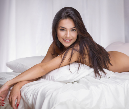 sexy woman on bed: Portrait of sexy brunette woman with long hair and glamour makeup.