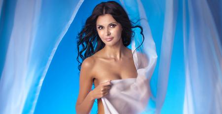 sexy nackte frau: Attraktive reizvolle Frau nackt im Studio aufwirft. Blick in die Kamera. Mädchen mit dem langen lockigen Haar. Zarte Dessous.