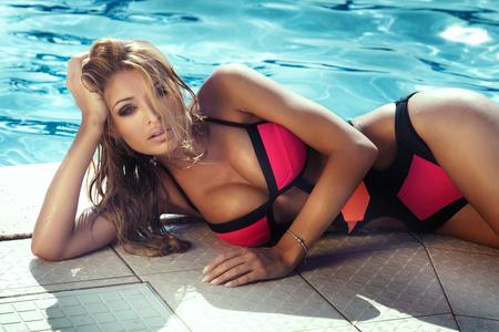 Beautiful breasts: phụ nữ tóc vàng xinh đẹp với trang điểm quyến rũ và mái tóc dài. Sexy nhìn. Cô gái trong bộ đồ bơi.