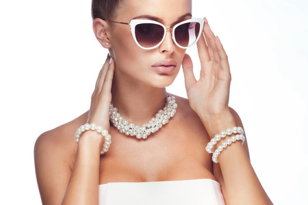 Beauty portrait of elegant attractive blonde woman wearing pearls and stylish sunglasses.