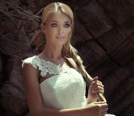 Beautiful blonde woman posing in white wedding dress outdoor. Fashionable dress.