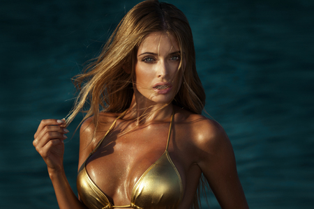 beauty breast: Portrait of beautiful blonde woman with glamour makeup and long  hair. Sexy look. Girl in gold swimsuit.