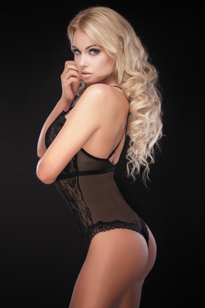 black breast: Beautiful blonde woman posing in sexy black lingerie, looking at camera. Perfect slim body. Long healthy hair. Glamour makeup.