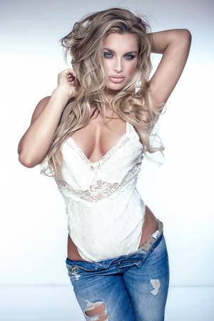 hot breast: Модная сексуальная блондинка женщина позирует в джинсы, глядя на камеру. Студия выстрел.