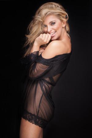 Schöne blonde Frau in sexy schwarzen Dessous posiert, die Kamera betrachten. Perfekte schlanken Körper. Lange gesundes Haar. Glamour Make-up. Standard-Bild - 51889083