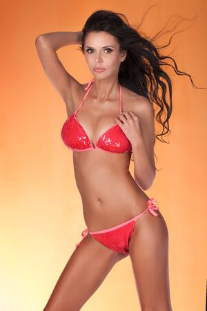 young girl nude: Sensual brunette woman posing in fashionable bikini. SLim fit body. Summer concept. Studio shot.