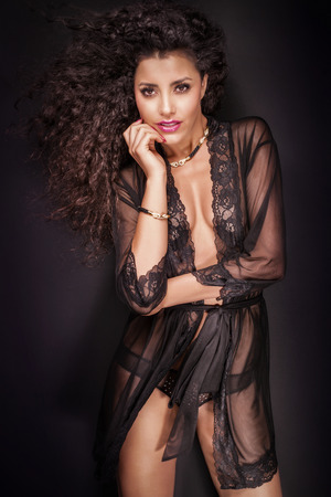 hot breast: Attractive african american woman posing in elegant black lingerie, looking at camera. Фото со стока