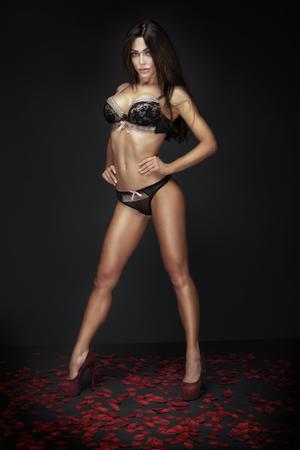 seni: Sexy bella signora bruna posa in lingerie elegante, in piedi su petali di rose rosse. San Valentino.