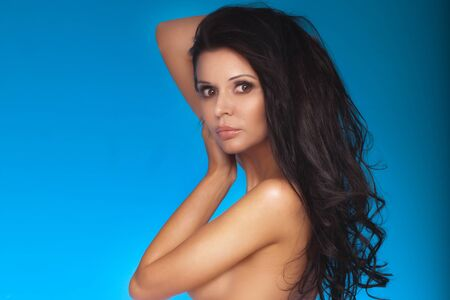 nude female body model: Portrait of sensual beautiful brunette woman with brown eyes and long hair. Blue background.