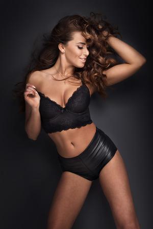 femme noire nue: Belle jeune femme brune aux longs cheveux bouclés posant dans la lingerie. Studio shot.