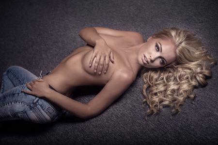 ragazza nuda: Sexy bionda bella donna distesa nuda sul pavimento, guardando a porte chiuse.
