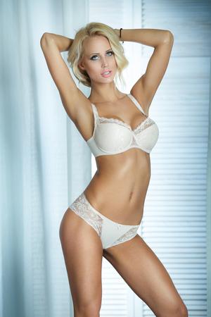 nudo integrale: bella donna sensuale posa in lingerie romantica, guardando a porte chiuse. corporeo ideale.