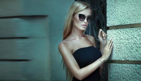 coiffer: Mode femme blonde posant en plein air, le port mini robe et lunettes de soleil élégante.